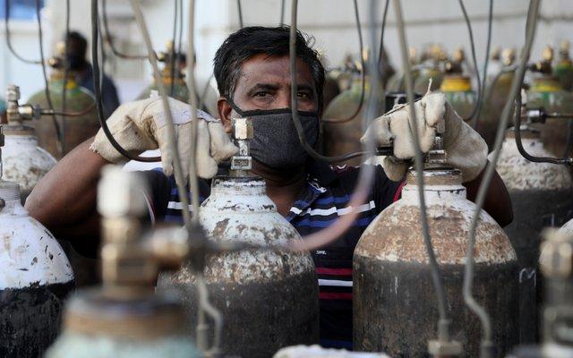 Ein indischer Arbeiter füllt Sauerstoffflaschen für Coronakranke ab.